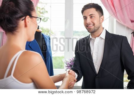 Cheerful young businessman is congratulating a skilled designer