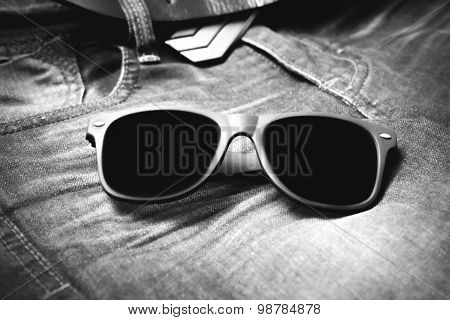 sunglasses on jean trousers black and white tone color style