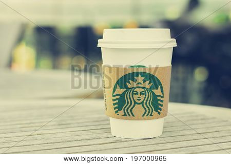Bangkok Thailand - Feb 26 2015 : Starbucks take away coffee cup with logo on sleeve Starbucks brand is one of the most world famous coffeehouse chains from USA. (vintage style color image with soft focus)