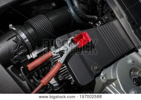 red clamp on car battery. for charging battery car with electricity.