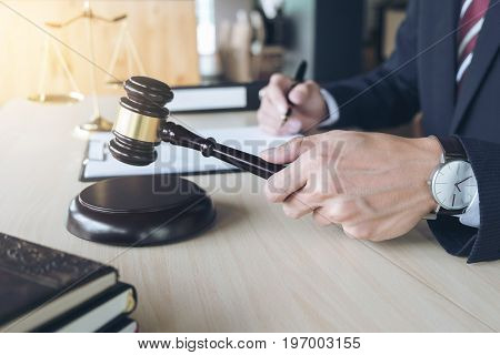 Close up of hand Judge hitting gavel and scales of justice Book Report the case with note paper on wooden table Law and justice concept.