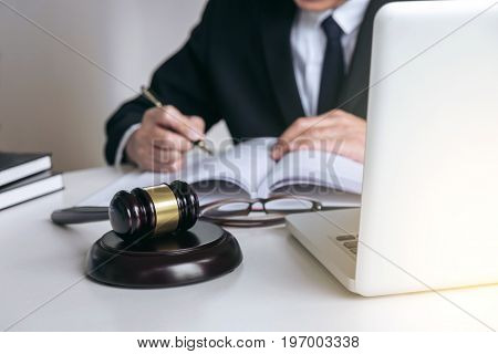Close up of gavel Male lawyer or judge working with Law book report the case on table in modern office Law and justice concept.