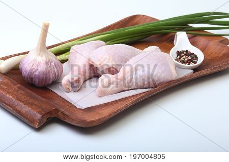 raw chicken legs with spices, garlic and green onion on a wooden board. Ready for cooking