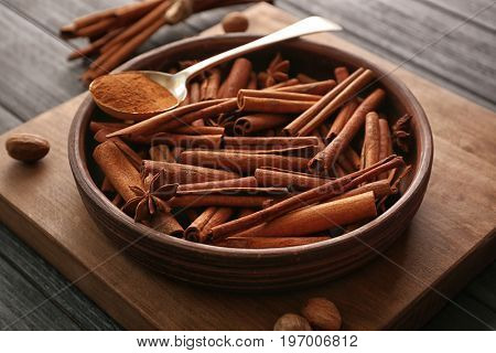Bowl with cinnamon sticks on wooden table