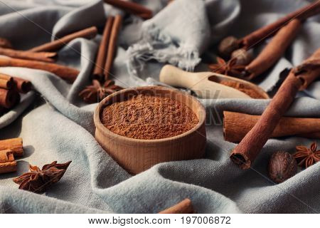Wooden bowl with powdered cinnamon, sticks and anise on tablecloth