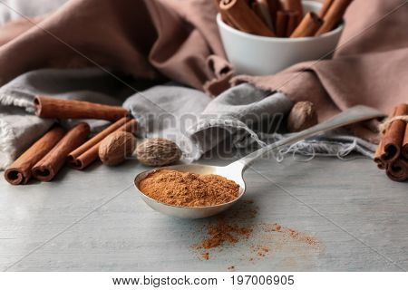 Metal ladle with powdered cinnamon on grey table