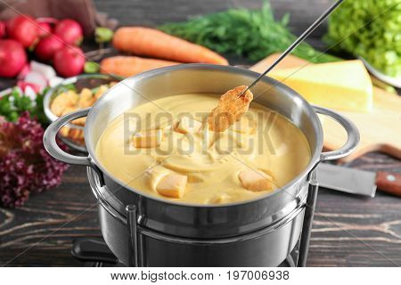 Pot of delicious cheese fondue with dipped rusk on wooden table