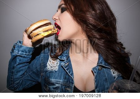 Closeup portrait of woman eating burger. Unhealthy diet of people and junk food concept
