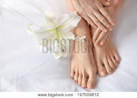 Female legs with flower on white fabric. Epilation concept