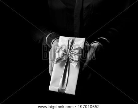 Black Mania. female hands isolated on black background showing present box