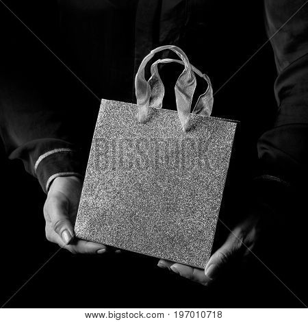 Black Mania. female hands isolated on black showing shopping bag