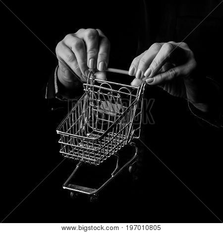 Black Mania. woman hands isolated on black showing mall shopping cart