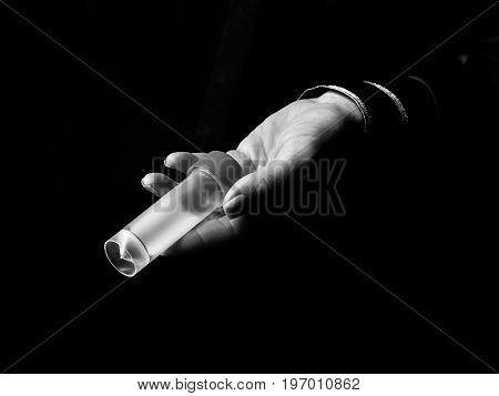 Woman Hand Isolated On Black Showing Sample Jar