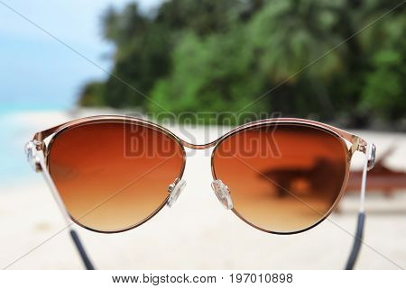 Modern sunglasses and blurred tropical beach on background. Summer vacation concept