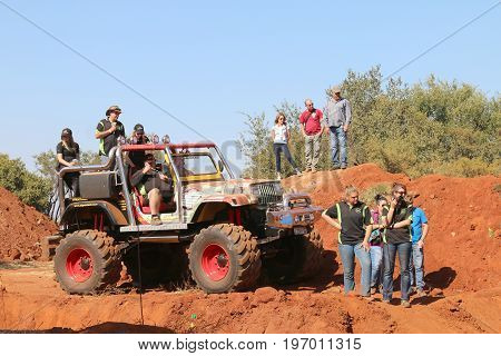 Event Commentator On Big Foot Large 4X4 With Spectators Looking At Event.