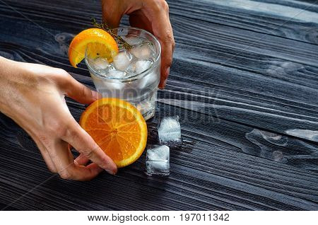 Serving of a cold beverage with ice and citrus fruits on a dark wooden table. Bartender's hands at work close-up.