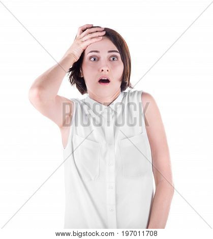 A terrified young woman isolated over the white background. A scared brunette lady holding her head in shock and confusion. An overwhelmed gasping female in a casual light blouse.