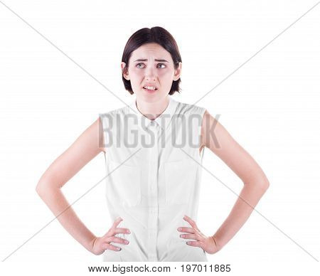 A confused posing brunette female isolated over the white background. An angry and strict lady with hands on hips. A professional and disgusted woman in a light casual blouse.