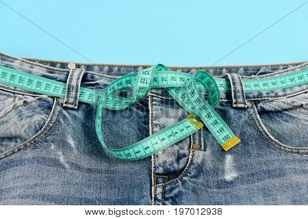 Jeans With Blue Measure Tape Fastened Instead Of Belt.