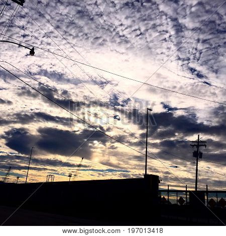 urban scene with clouds and powerline silhouettes