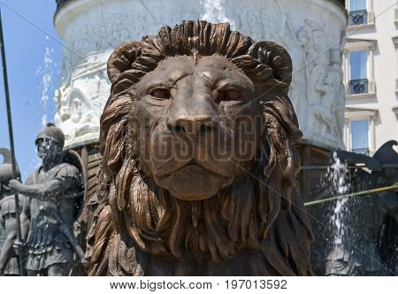 Bronze face of a lion and water fountain under the monument of Alexander the Great