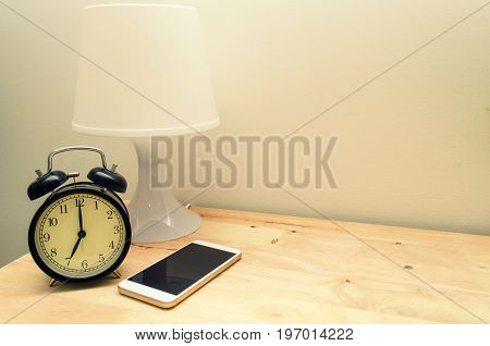retro style black alarm clock modern white lamp and mobile smart phone on wooden desk and white wall vintage color tone copy space selective focus