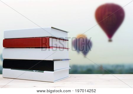 stack book on desk no labels blank spine with blurred view of hot air balloon in the sky background education back to school landscape nature and business concept selective focus copy space