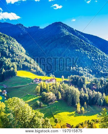 Charming chalet on a green grassy slope of the mountain. Rural pastoral in the Val de Funes, Dolomites. Warm autumn day. The concept of ecological tourism