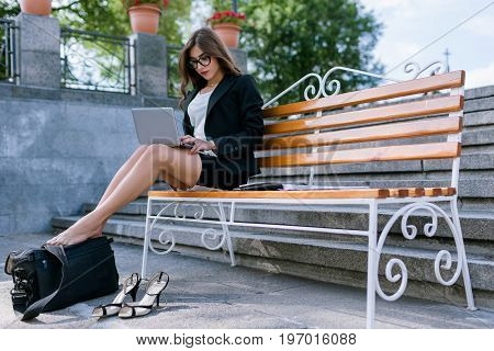 Young female with tired legs. Working on street, busy secretary. Overworked business woman