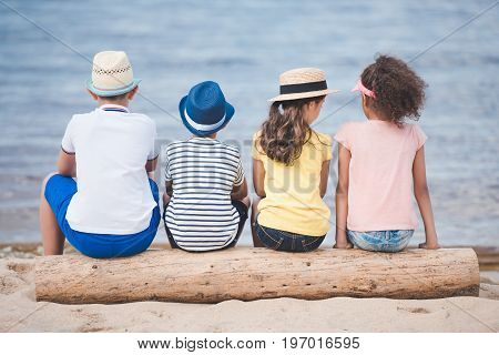 Back View Of Boys And Girls Sitting Together On Wooden Trunk At Seaside