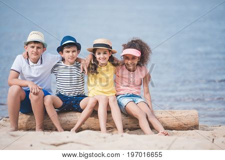 Multiethnic Children Hugging Each Other While Sitting On Wooden Trunk At Seaside