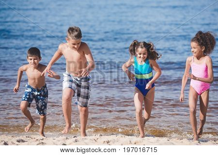 Multicultural Happy Children In Swimsuits Running At Seaside Together