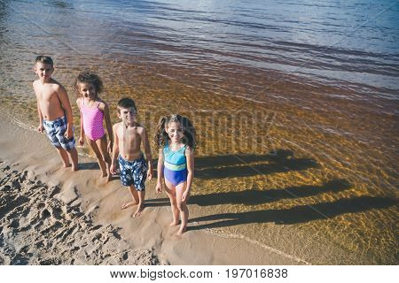 High Angle View Of Multicultural Kids In Swimsuits Standing On Beach