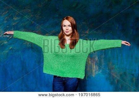 young pretty smiling redhead girl in greem pullover over dark blue background. beauty model woman with luxurious red hair. hairstyle. holiday makeup