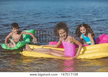 Multiethnic Little Children Swimming On Colorful Inflatable Mattresses At Sea Together