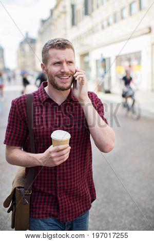 Man Walking Along City Street Talking On Mobile Phone