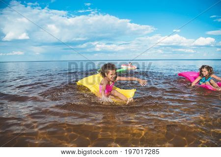 Multicultural Little Girls Swimming On Inflatable Mattresses At Sea Together