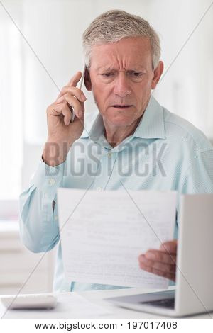 Unhappy Senior Man On Phone Querying Bill