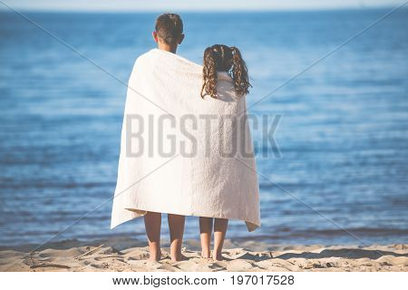 Back View Of Boy And Girl In Towel Standing Together On Seashore
