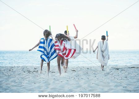 Back View Of Children With Towels As Superhero Robes And Water Toys In Hands Running On Beach