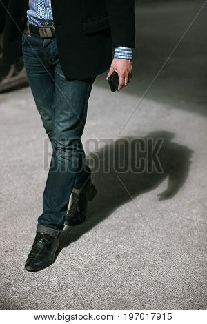 Modern communications. Businessman on street, unrecognizable male walking with mobile phone
