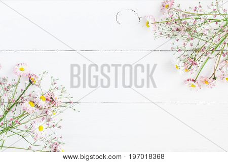 Flowers composition. Frame made of pink gypsophila flowers and daisy flowers on white wooden background. Flat lay top view copy space