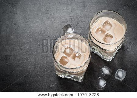 Irish cream liqueur in glasses with ice on black.