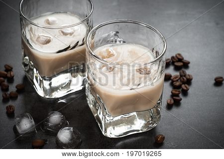 Coffee liqueur in glasses with ice and coffee beans on black.
