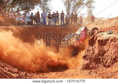Red Car Climbing Out Steep Dugout, Kicking Up Sand And Dust