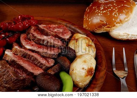 fresh roast bbq beef meat ribeye steak on wooden plate served with tomato juice in wooden cup, boiled broccoli, baked tomatoes and potatoes, white bun, and red wine glass on light walnut wooden table
