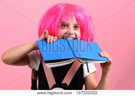 Pupil With Pink Wig. Girl Bites Big Blue Book.