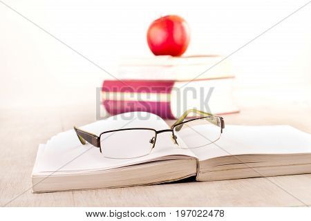 Eyeglasses On Open Book On Table