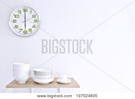 Stack of white bowls plate and cup on wooden table and white background with clock.