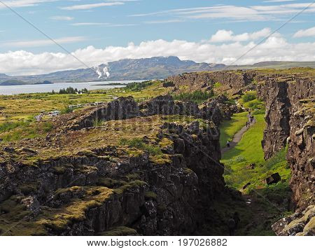 Thingvellir national park Iceland - north american - europe lithosferic rift - Mid-Atlantic Ridge with path and walking people and lake and mountain behind poster